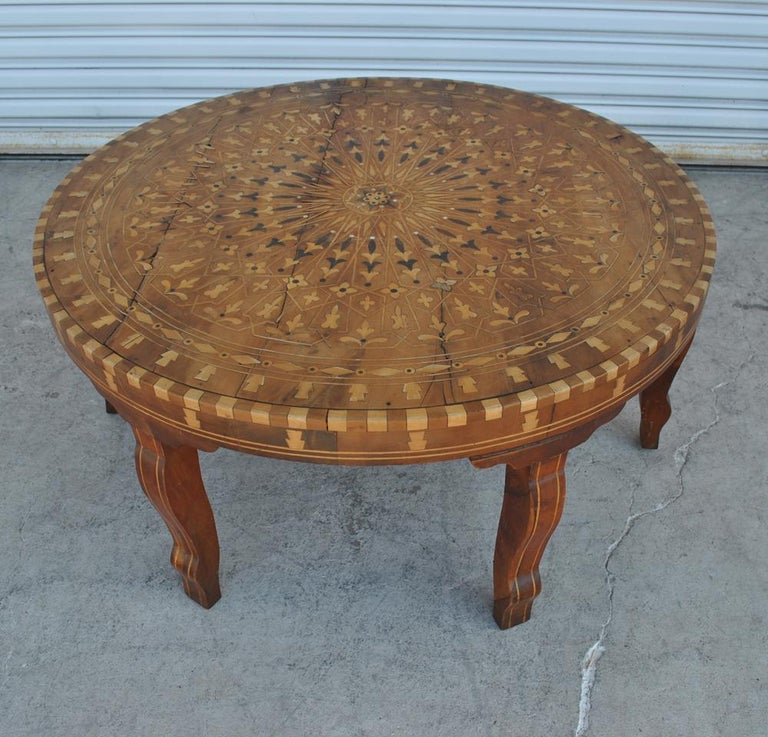 Handcrafted round Moroccan inlaid coffee table, cedar wood inlaid with various fruitwood parquetry and mother of pearl, very nice fine inlaid marquetry work with geometric designs and foliage. Coffee table from Essaouira, Morocco. The specialty of