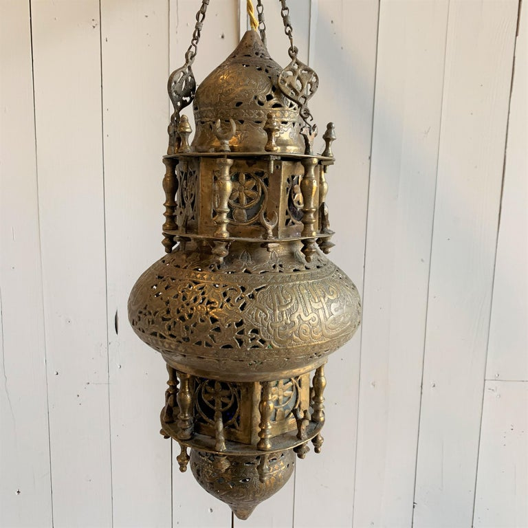 A Moroccan style hanging lantern in pierced and embossed brass with colored glass panes. Recently rewired.