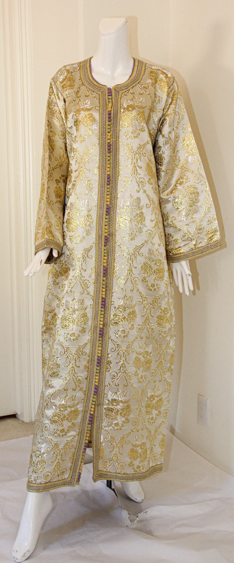 Moroccan vintage gold and silver metallic floral brocade dress kaftan with gold trim. Handmade ceremonial caftan from North Africa, Morocco. Vintage exotic 1970s metallic brocade caftan gown. The luminous cream and gold metallic caftan maxi dress