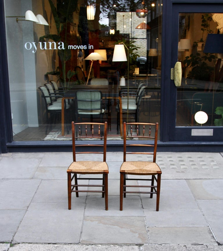 A pair of completely original 'Sussex' chairs designed Philip Speakman Webb circa 1860 and made by Morris, Marshall, Faulkner & Co. (later Morris & Co.), London, before 1900. The turned wood frames of the chairs are dark-stained solid beech and
