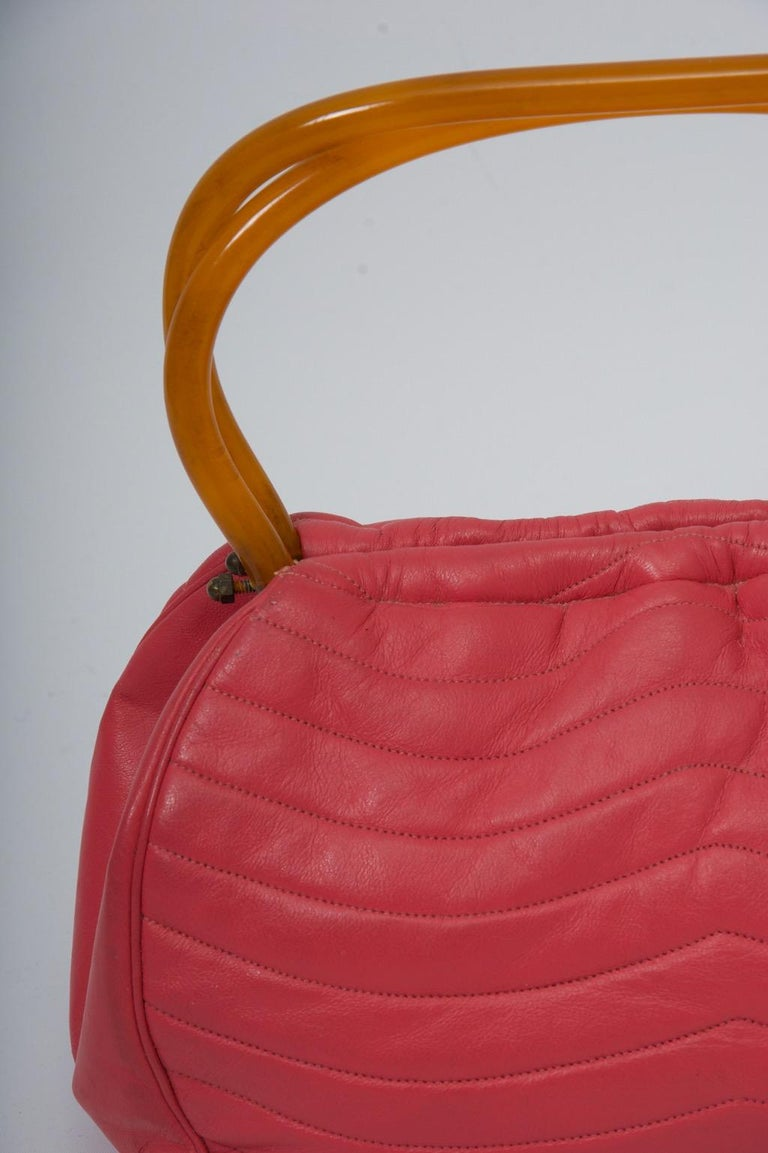 MM handbag c.1960s in dark pink, the leather featuring horizontal, curved stitching resulting in a quilted effect. The faux tortoise handles echo the shape of the bag and snap together to close. A coordinating faille interior has an attached money
