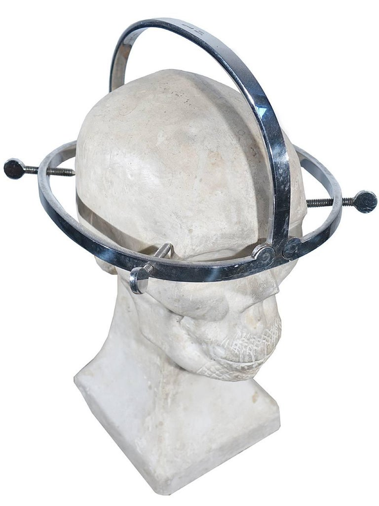 These devices were used by surgeons as well as morticians. This example is hinged and the sides fold up next to the top bow. The plaster skull is also included to display the device. This 1920s skull was used as a teaching aid for medical students