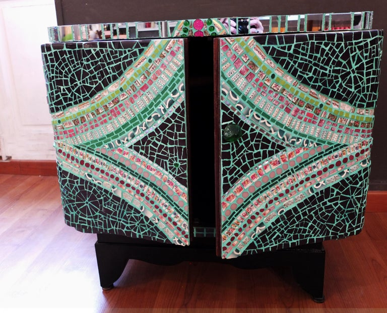 One of a kind Mosaic cabinet, created using an original vintage small customized wood Art Deco style cabinet covered in fragments of ceramic, porcelain dishes , mirrors, glass, etc. All these different materials are gather together and handcut one