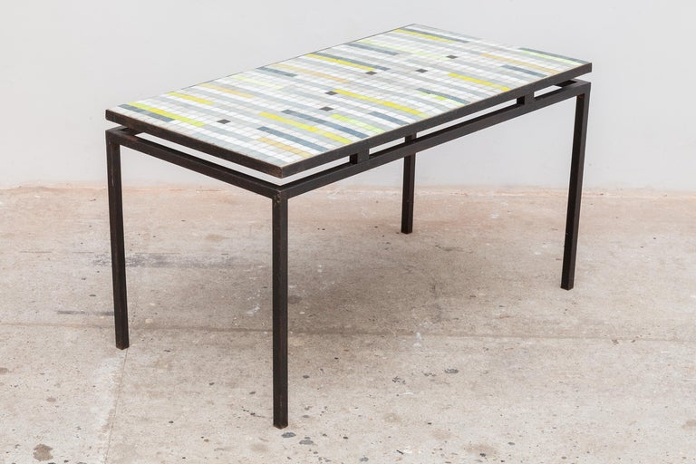 Vintage midcentury mosaic tile table. Striped design with neutral stone tile striped with blues and neon yellow. Floating iron frame. Dimensions: 91 W x 50 H x 47 D cm.