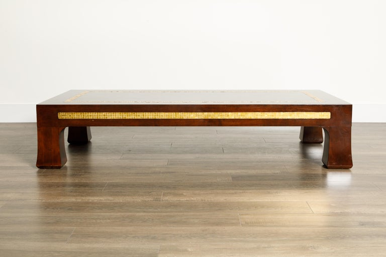 This spectacular deep brown walnut coffee table was designed by Edward Wormley for Dunbar, circa 1950s, and features Mid-Century Modern flared legs and golden mosaic tile inlay wrapping all four sides and on the table top. Signed underneath with the
