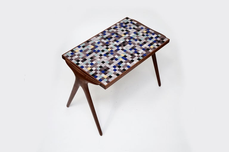 This rare gem of a side table is by Vladimir Kagan, during his early years with Hugo Dreyfuss featuring his highly-sought-after-by-collectors mosaic tiles on the table top and sculpted walnut frame for the table's body and legs. Produced in small