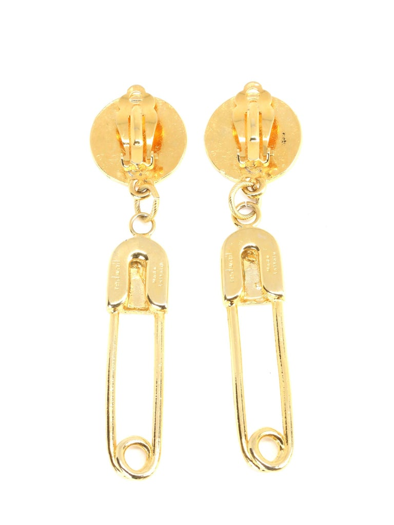 Long gilt earrings with safety pin motif from Moschino dating to the early 1990's. Measure approximately 3.33