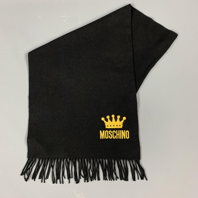 MOSCHINO scarf comes in black wool flannel with fringe trim and a yellow crown logo embroidery.   Very Good Pre-Owned Condition.  64 x 16 in.