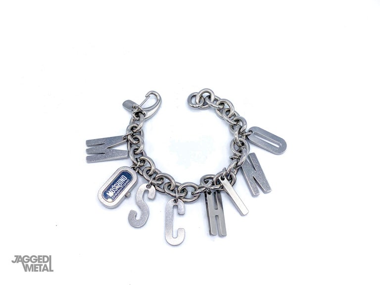 Moschino 1990s Vintage Charm Bracelet  Amazing statement piece from the iconic house of Moschino. Doubles up as a bracelet and watch.  Detail -Made in the early 2000s -Cast from stainless steel metal -8 charms which spell out the letters