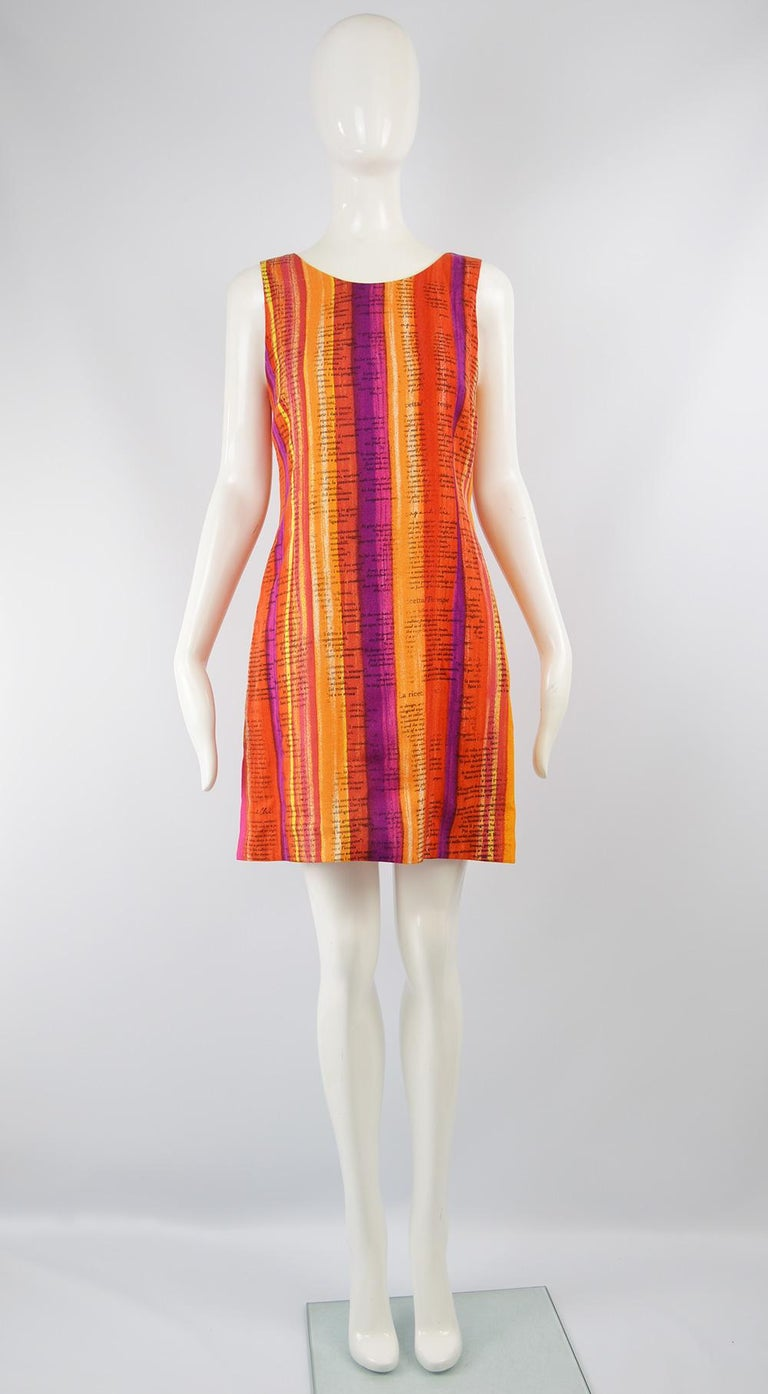A bold and fun vintage women's dress from the 90s by Moschino for the Cheap and Chic line. In a rayon fabric that is woven in such a way that it feels like linen and has watercolor inspired stripes in hues of oranges, purples, reds and white to