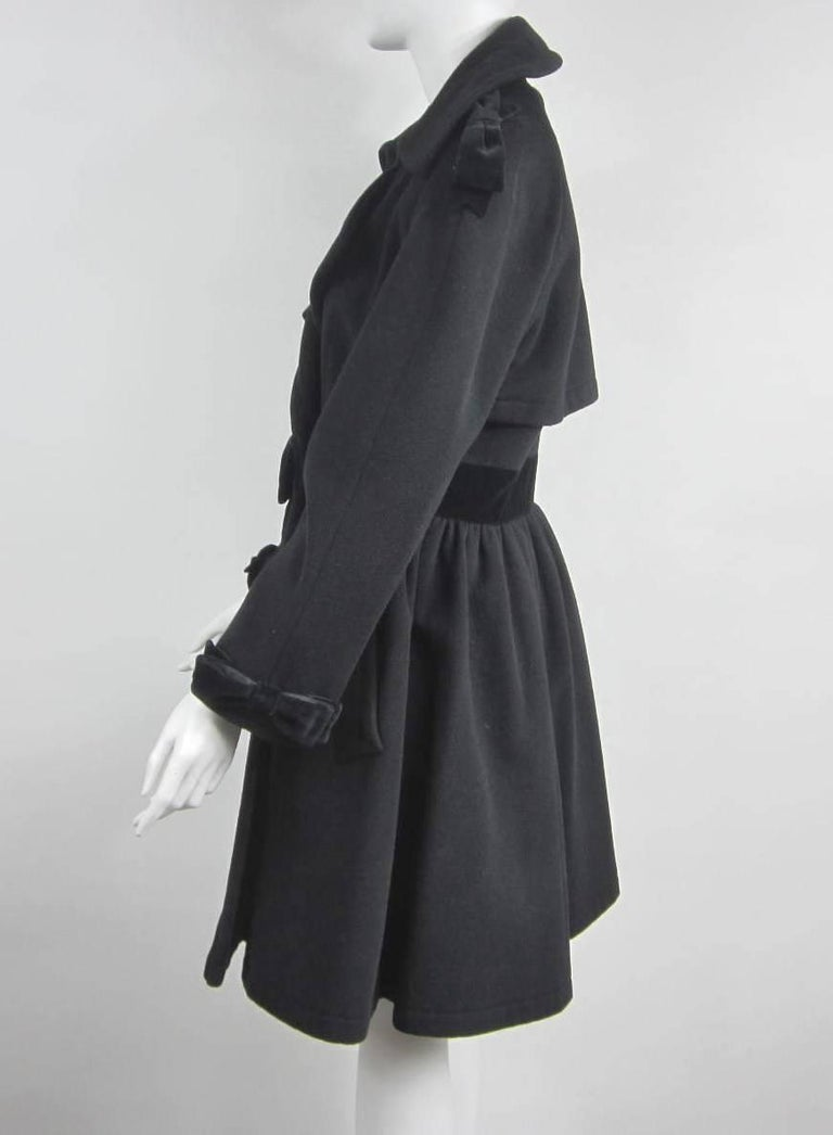 Stunning Black Wool and Velvet Moschino Coat. Bow trims Collar, Cuffs and Belt Measuring 36 in Bust / 30 in Waist / 37 in Length / 23 in Sleeves. Please be sure to check our storefront for more fashion as we have both Vintage and Contemporary