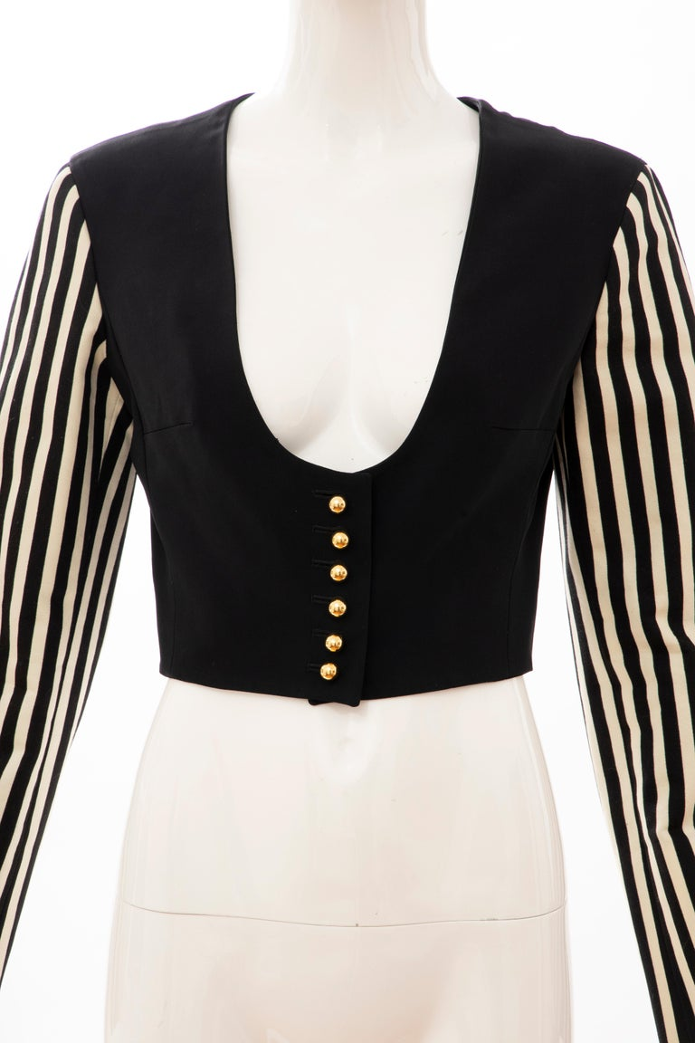 Moschino Couture, Circa: 1994 black cotton cropped brass button front jacket with acetate & rayon faille black & white striped sleeves and fully lined.  IT. 42, D. 38, FR. 38, GB. 10, US. 8  Bust: 35, Waist: 27, Shoulder: 15.5, Sleeve: 23.5, Length: