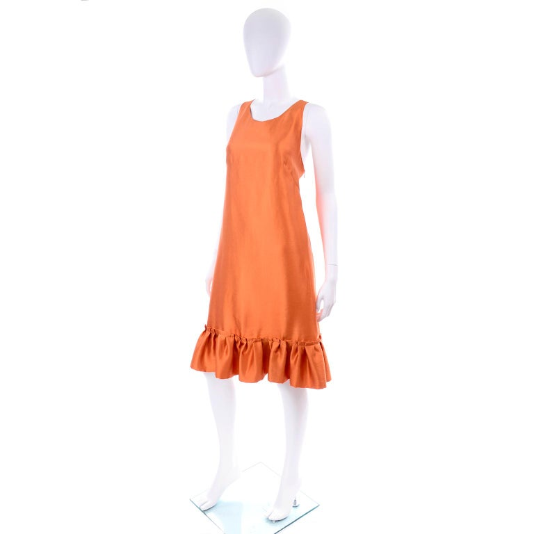 This is a gorgeous Moschino orange tent dress with a ruffled hem and a back bow.  The dress has lovely pleat detail in the back and closes with a side zipper. This fully lined dress was made in Italy and labeled a US size 12.  We estimate it to fit