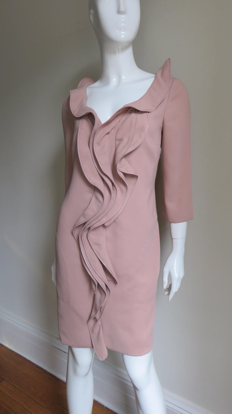 A great unique dress in nude tan from Moschino.  It has a V neck surrounded by a matching zipper edged ruffle extending down the center front of the dress.  It has side seam pockets, 3/4 length sleeves, matching nude silk lining and slips on over