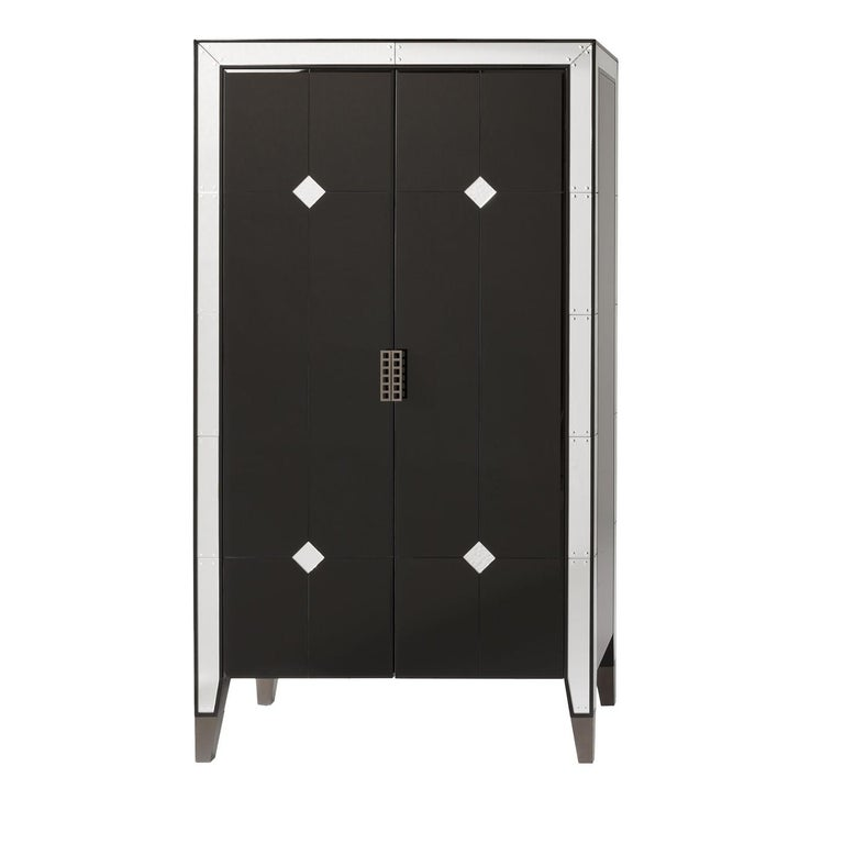 This exquisite cabinet bar has the flair and sophistication of the art deco style and is made entirely in wood with a black, glossy finish. Glass accents run around its edges and down to its feet with mirror inserts that were inlaid and given a