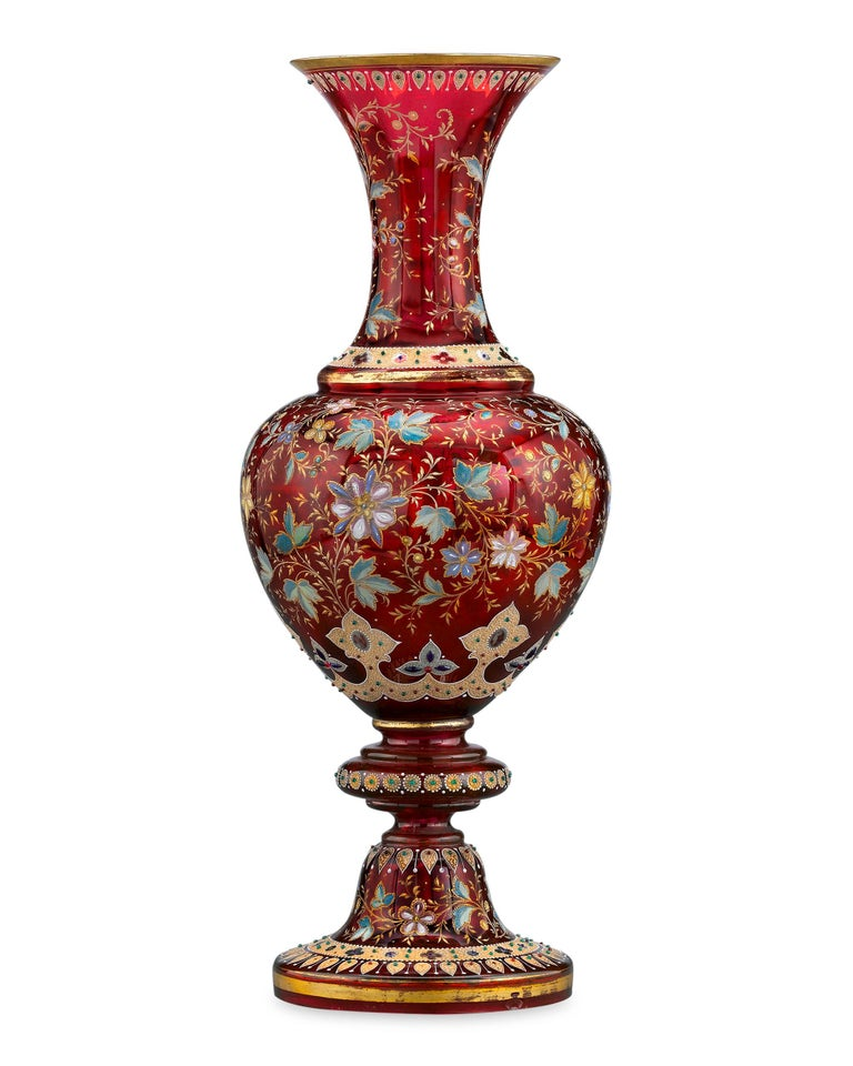 Almost certainly made as an exhibition piece, this monumental Moser ruby glass vase boasts a gilt-accented design of textured oak leaves and flowers, all enclosed by textured bands of jeweled gilding. Formed in a classical urn shape in Moser's
