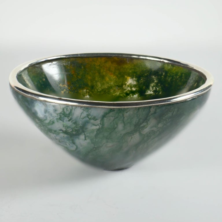 A charming bowl carved out of moss agate with a silver metal ring. Unmarked. Diameter 3