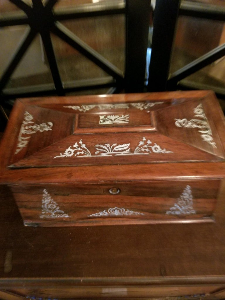 Beautifully executed, this mother of pearl inlay tea caddy does it all. In good condition, it has all of its parts: The individual containers and even a footed waste bowl. The details surround the box and is a wonderful presentation piece. In good