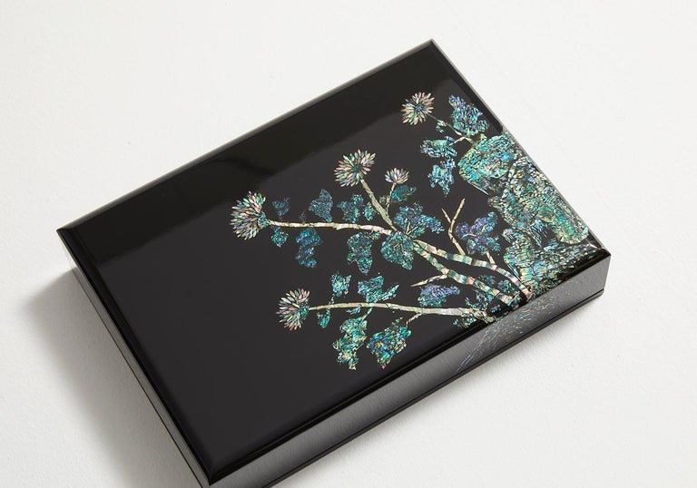 This artwork applied the method of striking and scouring to the carefully selected pieces of the iridescent mother of pearl, to create a wooden box depicting chrysanthemum flowers, one of the four gracious plants symbolizing strong integrity and