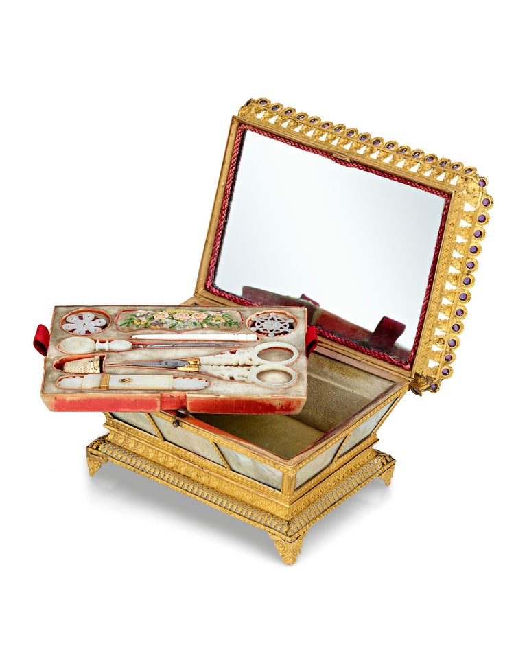 This captivating Palais Royal sewing nécessaire is crafted of engraved mother of pearl mounted in rich doré bronze. The hinged box contains a removable tray lined with velvet that holds an assortment of exquisitely decorated mother-of-pearl and gilt