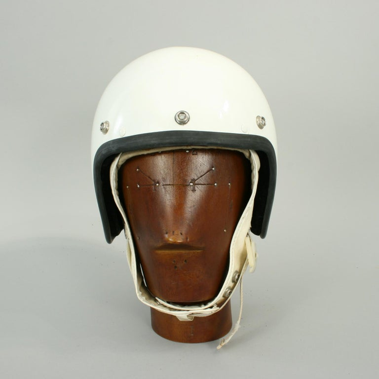 Vintage Cromwell motorcycle crash helmet. A white open face Cromwell motorcycle helmet with snap poppers for the addition of a peak. The helmet is with soft fabric interior with Cromwell trade label. Size 7, type G24 A. There is a goggle strap at