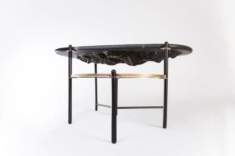 This coffee table has a mountain hand-carved underneath. The tabletop is made of a carved block of Monterrey marble or Huichapan marble according to the material availability. The metal pieces are powder coated in matte black and the other metal