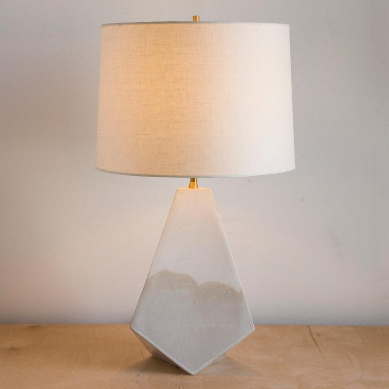 This geometric ceramic 'Mountain' table lamp is made from a sandy beige clay, formed into a dramatic pyramid shape, and featuring an organic matte finish accented by hand-poured glossy white glaze. Each piece is individually handmade and entirely