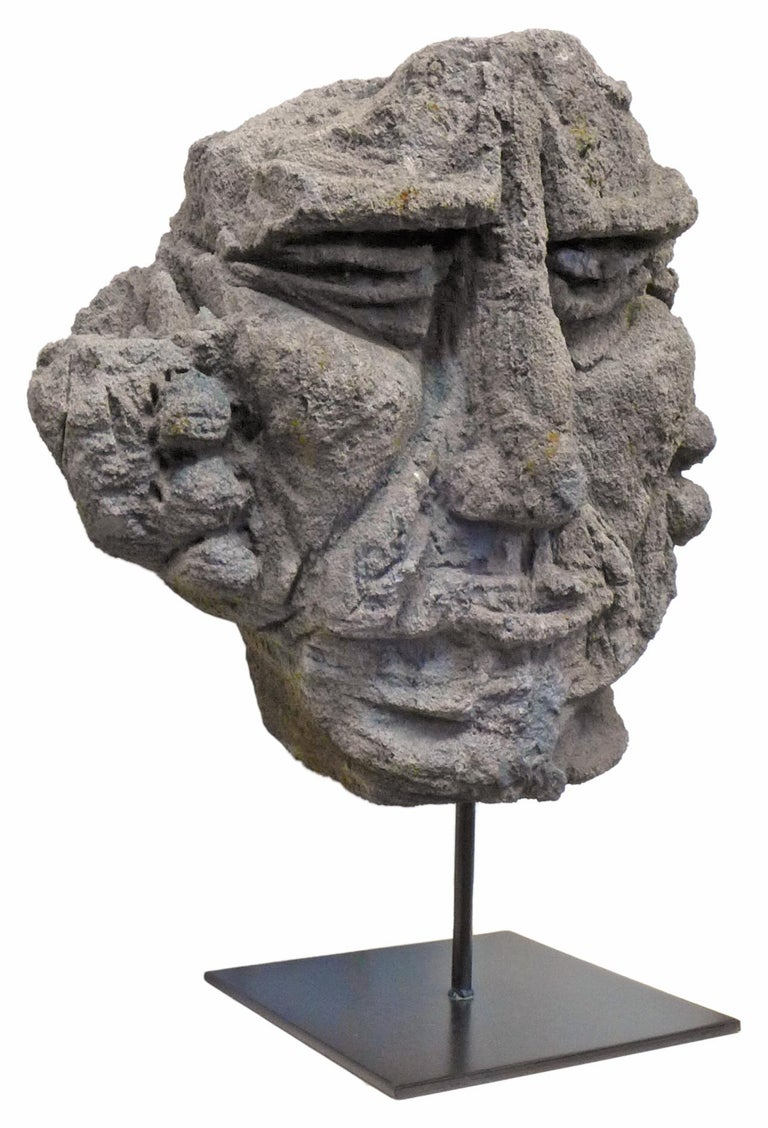 An incredible, mounted, carved lava stone face sculpture. Origin unknown, though likely Polynesian, a wonderful, primitively carved piece with deep, exaggerated features. Seemingly part of a larger work, possibly a bas relief. Set on a contemporary,