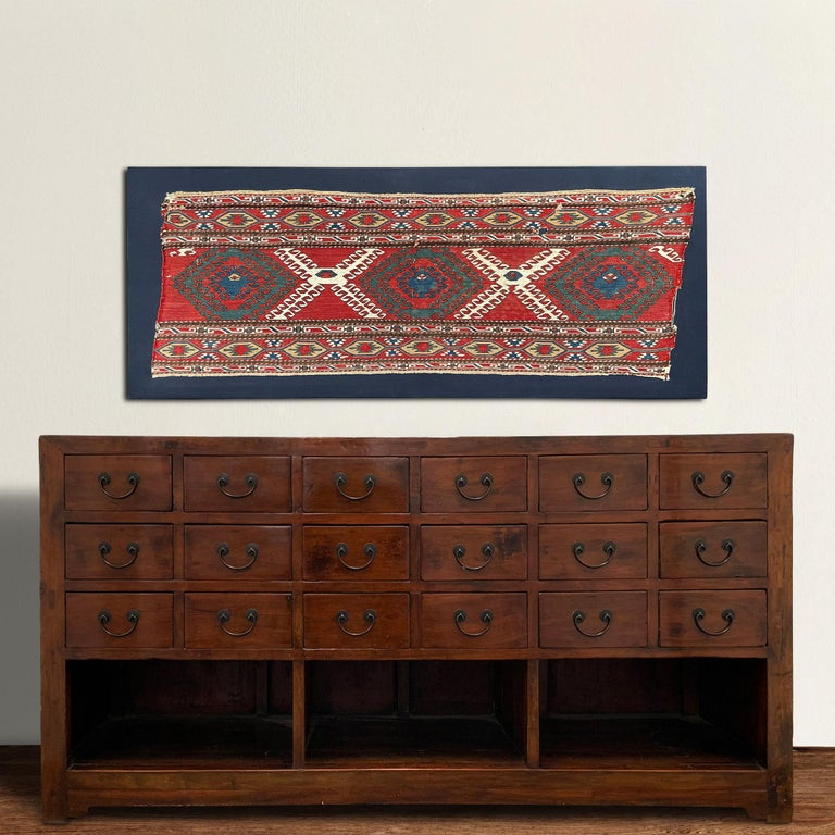 A bold mounted 19th century Azerjaibjani Soumak rug fragment containing several stylized floral patterned motifs and stripes containing petite floral and geometric patterned stripes, all woven in light and dark indigo, crimson, green, white, and