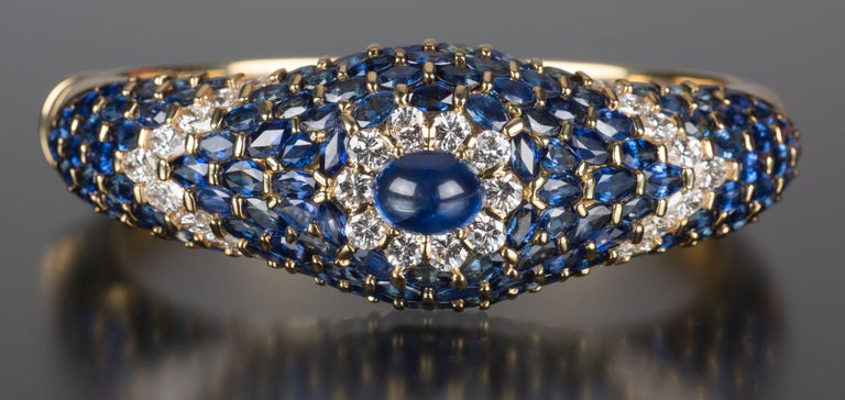 The House of Moussaieff is known for its deep understanding of fine and rare gemstones. This substantial vintage hinged bracelet illustrates their expertise as it makes maximum use of vivid blue sapphires and brilliant white diamonds. The
