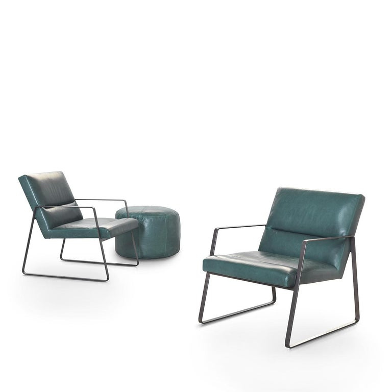 The sophisticated lines and contemporary structure of this emerald green leather armchair is almost reminiscent of a movie theater seat with its slightly-reclined backrest. Large minimal metal trapezoids serve both as armrests and a base for the