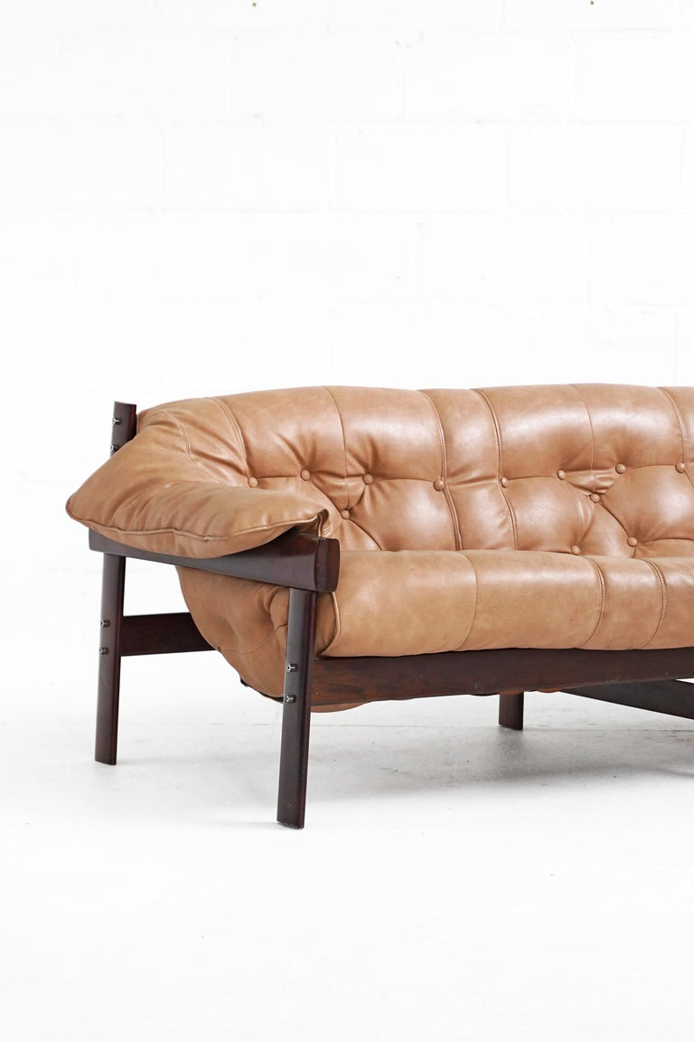 Three seater sofa designed by Percival Lafer reupholstered at some point in it's life, identical and beautifully as per the original design in an extremely high quality vinyl. This piece dates to the 60s-70s and is in good vintage condition with 2