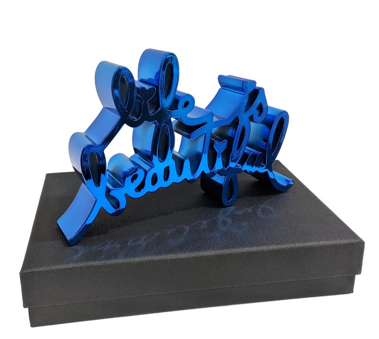 Hand signed, numbered and dated on bottom by the artist. Edition of 100.  The Life is Beautiful sculpture is made from durable cast resin, thermal coated with reflective metallic finish. Includes original box and plexiglass display.   Artwork is in