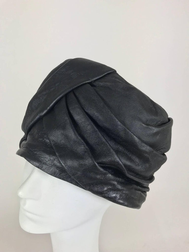 Mr John Jr black leather turban style hat from the 1960s. Depending on your head size (measure around your head approximately at your hair line), the hat will pull down like a turban or sit on top of your head. This hat is draped and pleated and is