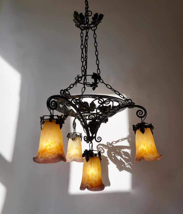 This sensational early French Art Deco chandelier was designed and signed by Muller Frères. It features a black wrought iron base with stylized floral and chain detailing. It has four frosted glass