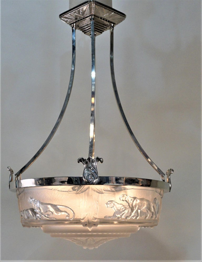 Frost glass in clear and frost features panthers, nickel on bronze frame chandelier. Height can be adjusted by cutting the rods. Eight lights 60 watts max each.