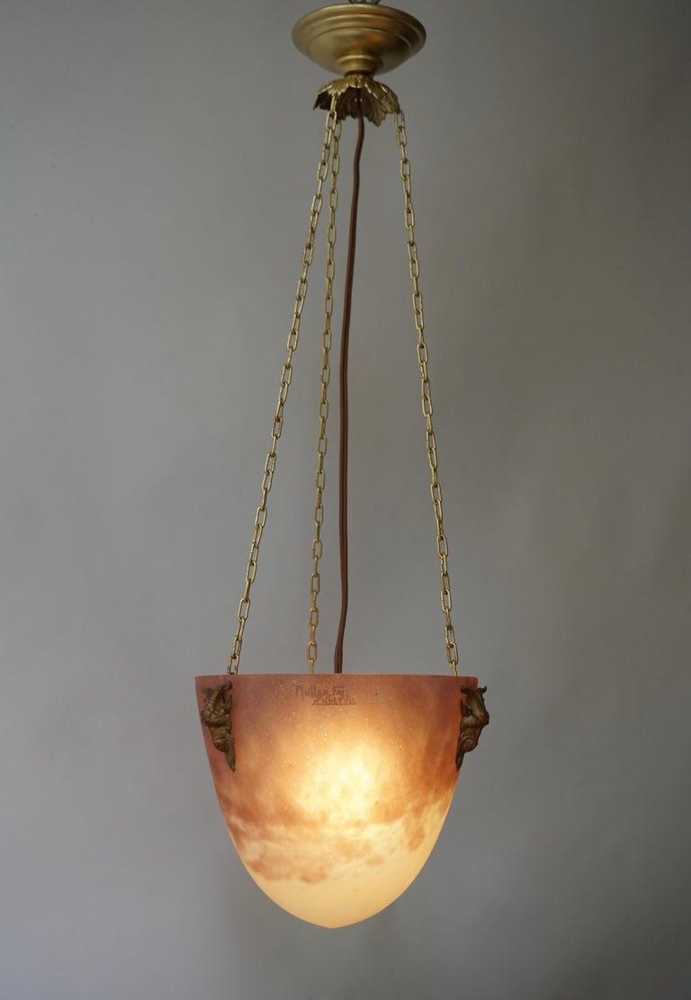 Rare French Art Deco pendant by Muller Frères, Luneville, France, early 1920s. Mottled glass shade, powders are applied between two layers, that comes hung at its original solid bronze fixture with three ram heads at the ends. The best colors by