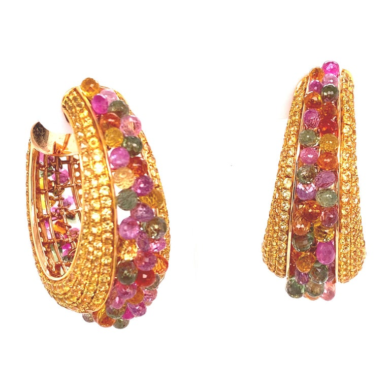 Stunning colorful sapphire hoop earrings are crafted in 18 karat yellow gold. The earrings are set with round brilliant cut yellow sapphires down the sides of the hoops. The middle of the hoops feature briolette cut multi-color sapphires. The