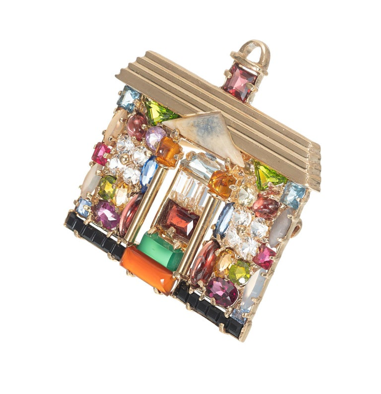 Multi gemstone pendant brooch. House design setting that can be worn as a brooch or pendant.     1 rectangular Chrysophase  1 rectangular Carnelian  1 emerald cut garnet  4 Marquise translucent quartz  2 oval and 2 marquise garnets  1 triangular