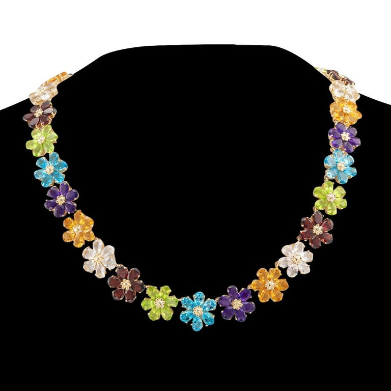 Multi color gemstone flower link and gold necklace circa 1990.  DETAILS:  GEMSTONES:  set as individual flower head-shaped links comprising pear shaped amethyst, blue topaz, citrine, garnet, peridot, and quartz.  METAL:  14-karat yellow
