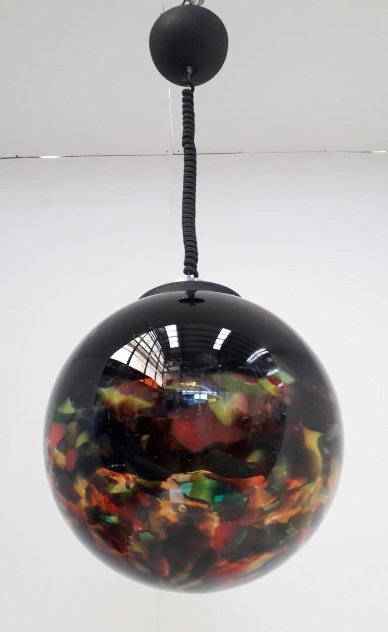 Italian Murano glass globe pendant blown with black and multicolored hemispheres / Made in Italy circa 1960s Single light / E26 or E27 type / max 60W Diameter 14 inches / height 14 inches plus adjustable cable and canopy 1 in stock in Italy