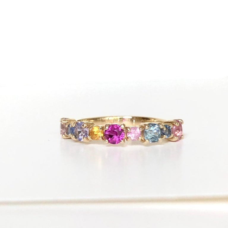 Beautiful round brilliant cut multi color natural sapphire with a half circle of round multi color candy sapphires 100% natural, weighing approx. 1.00 carat. This fabulous band is fashioned in 14K yellow gold mounting and 100% natural
