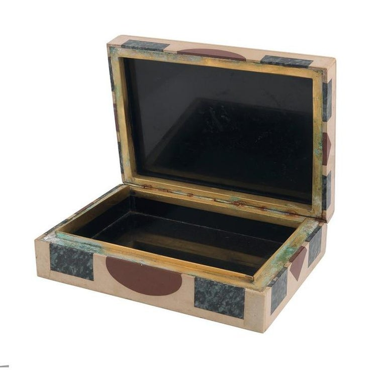 The present box is fabricated of brown marble and inlaid with different minerals such as: lapis lazuli, red jasper and green agate. The hinged lid opens to reveal a lavagna lined interior. Measuring 17cm x 12,5cm x 5cm.