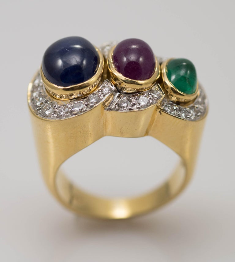 Ladies multi-stone and diamond ring in 18 karat yellow gold. Stamped 18k and weighs 18.1 grams. The colored stones are natural cabochon cut, 10 x 7mm blue sapphire, 8x 6mm ruby and 6.5 x 5mm emerald. On the sides are round brilliant cut diamonds,