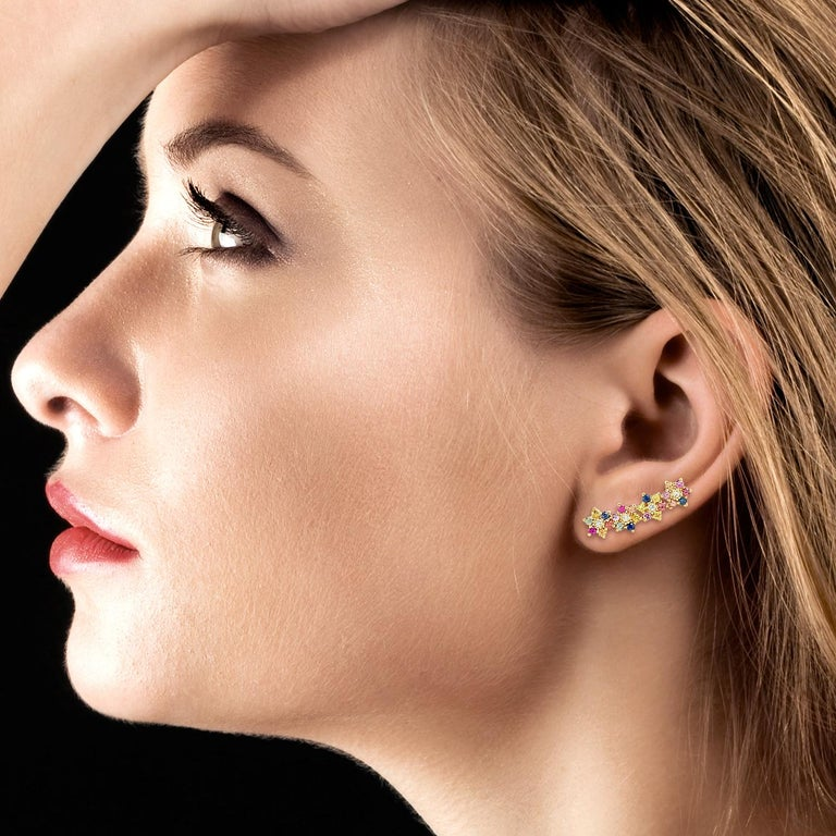 These flower ear climbers are handmade in 18-karat gold and beautifully detailed with .94 carats multi sapphire and .12 carats of glimmering diamonds. Show off their unique style by sweeping your hair back.  Please note that carat weights may