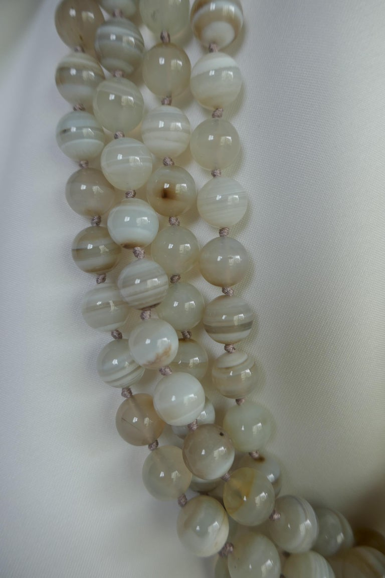 This necklace four strand multi-strand banded agate necklace is individually knotted with a tan silk thread and has a 925 sterling silver clasp. The banded agate beads are 10mm. The length of the necklace is 24 inches. This is the only one currently