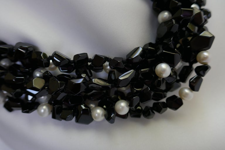 This black spinel nugget and white cultured pearl is a seven strand statement necklace. The white cultured (7.5mm-8mm) pearls are interspersed through out the necklace.  The necklace is individually knotted on black silk thread and has a 925