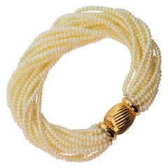 Multi Strand Pearl Wrap Bracelet with Decorative Yellow Gold Bow Tie Clasp