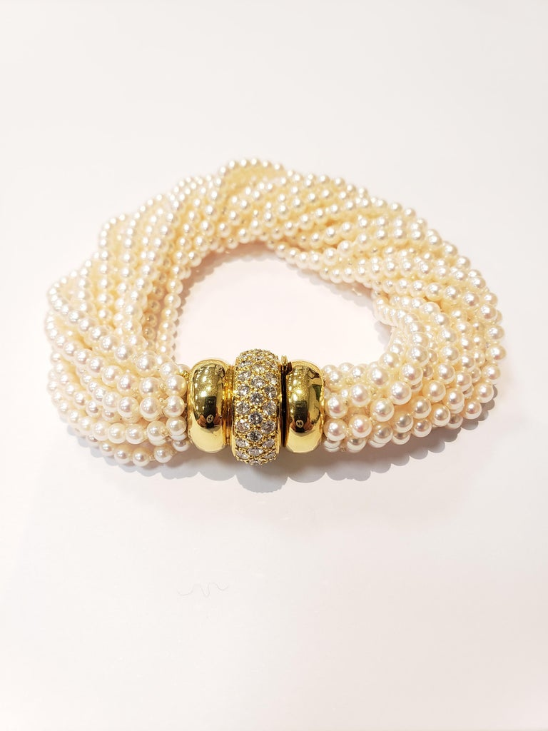 A 15 strand seed pearl bracelet with an 18 karat yellow gold and pave set diamond clasp. pearls are 3.4-3 millimeter. clasp center is fully set with diamonds all around. Bracelet measures 7.5 inches in length, but can be adjusted by twisting pearls