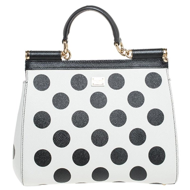This gorgeously designed Miss Sicily bag from Dolce & Gabbana is a handbag coveted by women around the world. It has a well-designed leather body adorned with polka dots pattern and rose patches. The front flap opens to a compartment with fabric